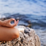 Woman doing yoga by water, lotus position, focus on hand on knee